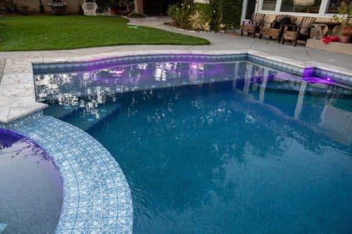 custom swimming pool with purple underwater lights
