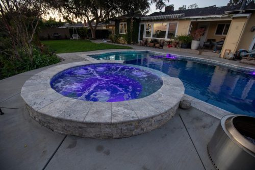 custom swimming pool with spa feature and underwater lights built by Orange County pool contractors
