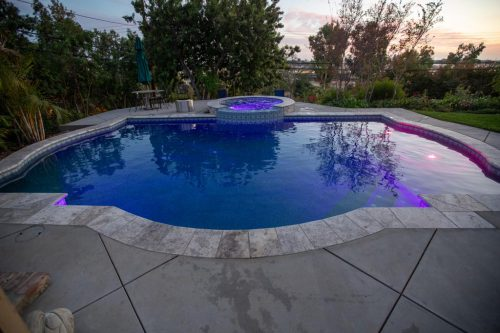 custom swimming pool with unique shape and purple underwater lights
