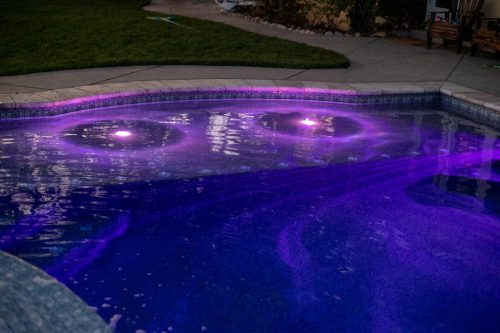 residential pool with purple underwater lights at night - built by Orange County pool contractors Pool Icons