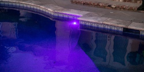 luxury swimming pool with purple underwater lights at night - built by Orange County pool builders Pool Icons