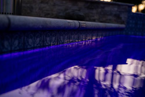 close up on surface of dark swimming pool water with purple lights - built by Orange County pool contractors