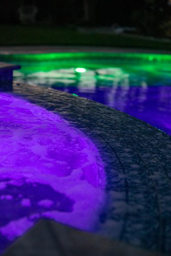 Orange County pool at night lit by green and purple underwater lights
