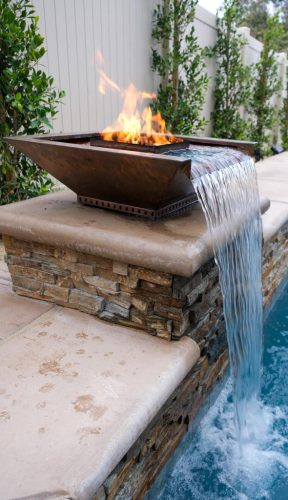 close up of poolside fire feature with waterfall in Los Angeles luxury pool