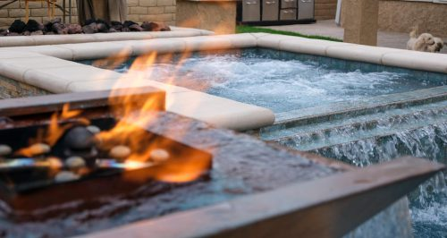 luxury swimming pool spa with fire feature in foreground built by Los Angeles pool contractors